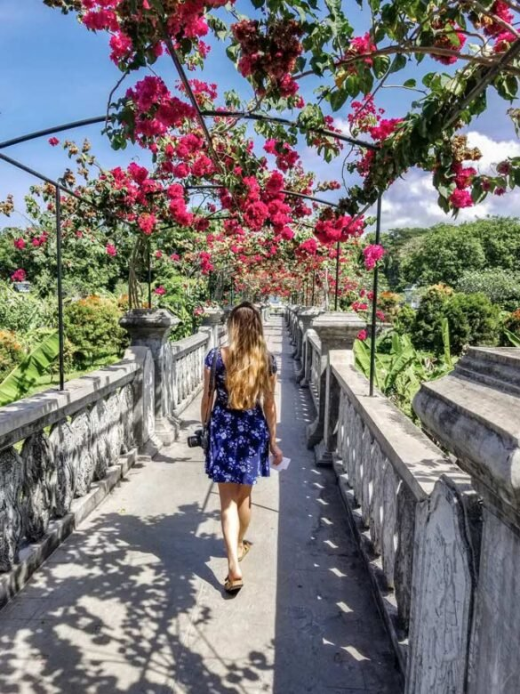 Bali Garden bridge to temple with pink flowers over head. Women walking down middle of bridge in blue dress.