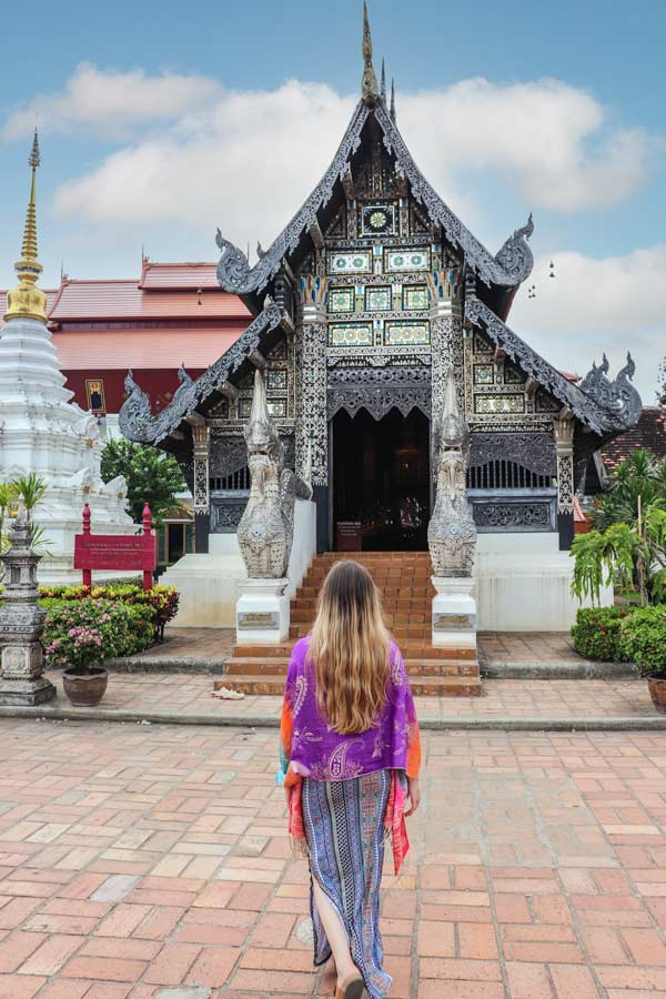 Chiang Mai Temple in Thailand that is bluish grey with metallic details. Women in front facing temple with purple shall covering shoulders, blue long skirt and long blonde hair.