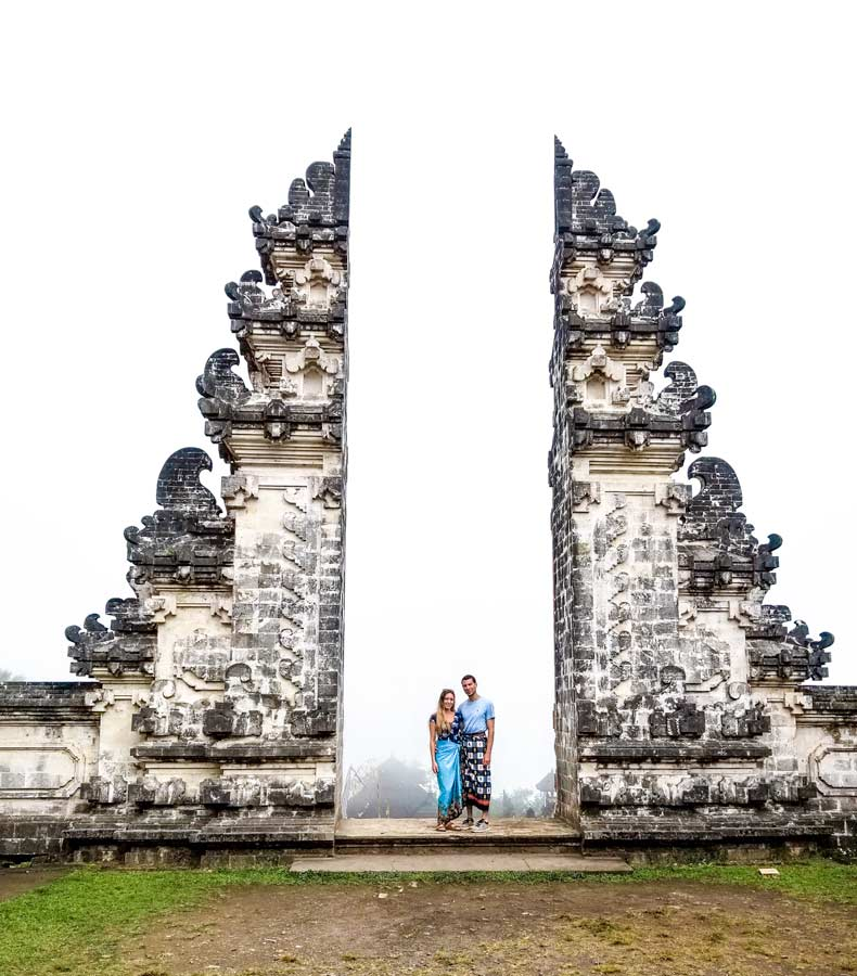 Gates of heaven in Bali. Man and woman standing in the middle with clouds in the background.