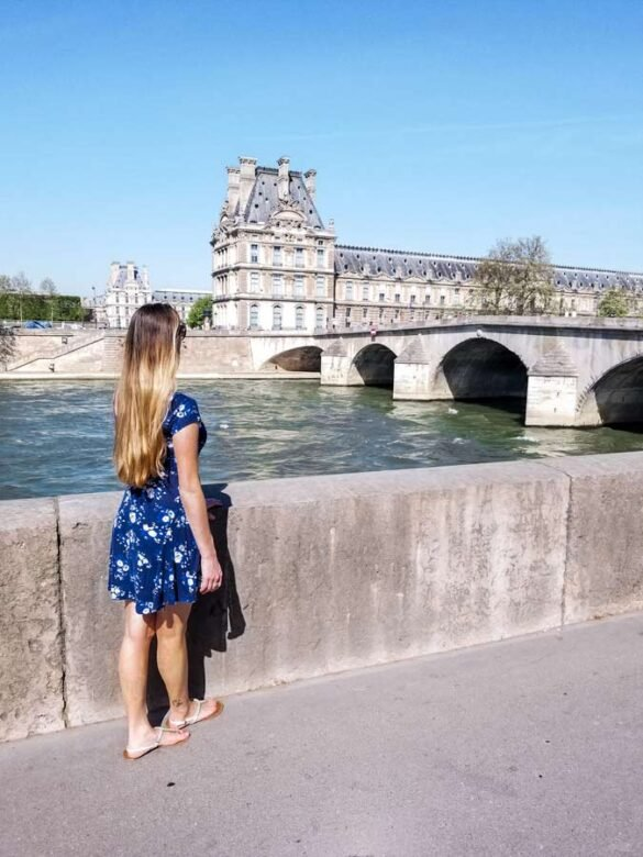 Paris travel inspiration. Women standing in blue dress looking at bridge.