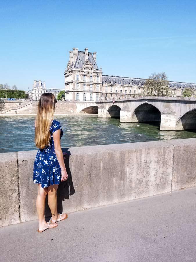 Paris travel inspiration. Women standing in blue dress looking at bridge.