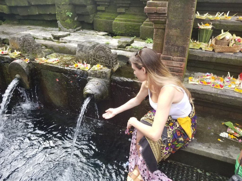 Putting holy spring water on head Ubud, Bali
