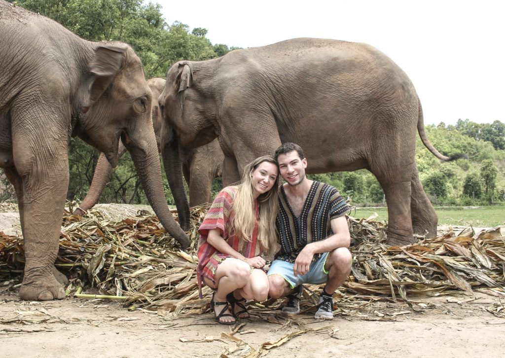 husband and wife kneeling down next to elephants that are eating