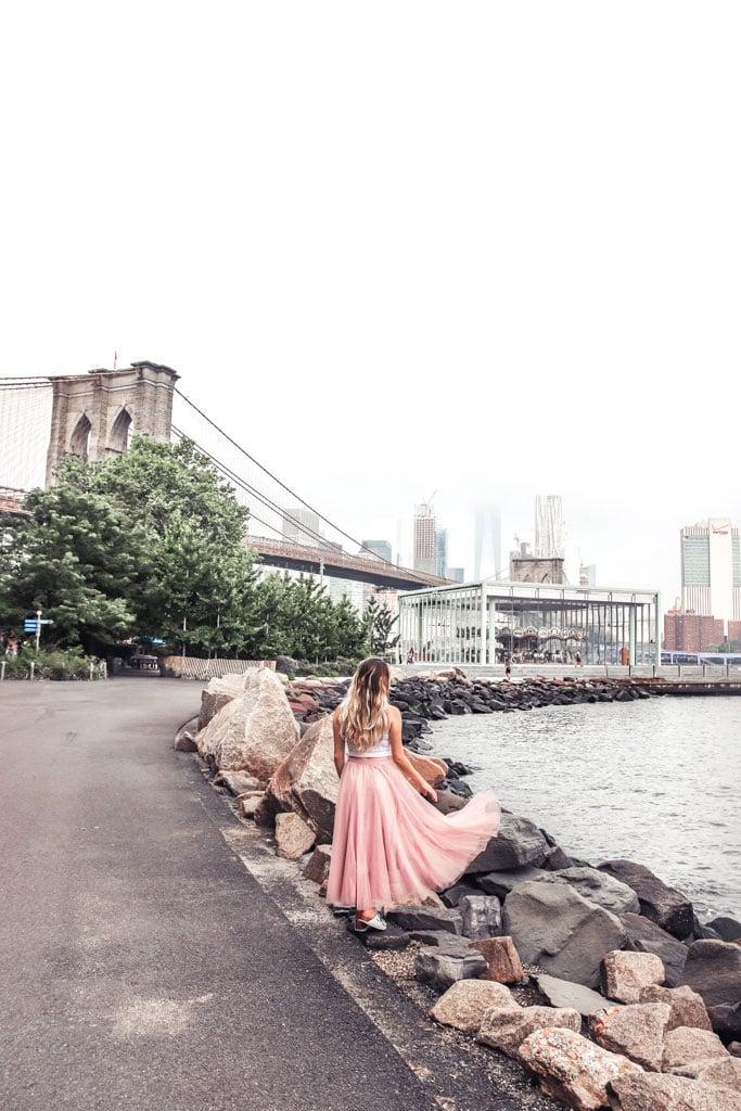 Brooklyn Bridge at Brooklyn Bridge Park NYC Instagrammable places. Woman looking at Brooklyn Bridge in pink skirt.