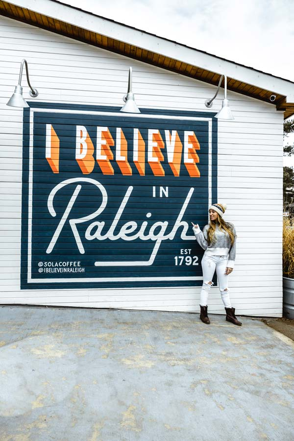 Insta-worthy I Believe in Raleigh Murals with woman standing in front. Mural is blue with orange and white letters.