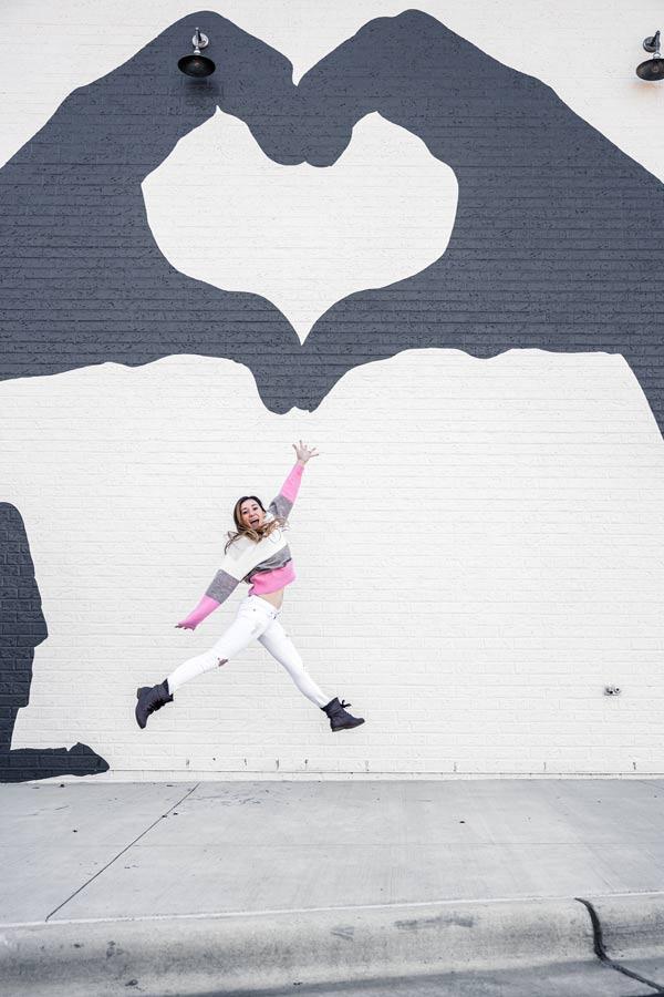 Heart hand mural in Midtown East Raleigh. Woman jumping under mural