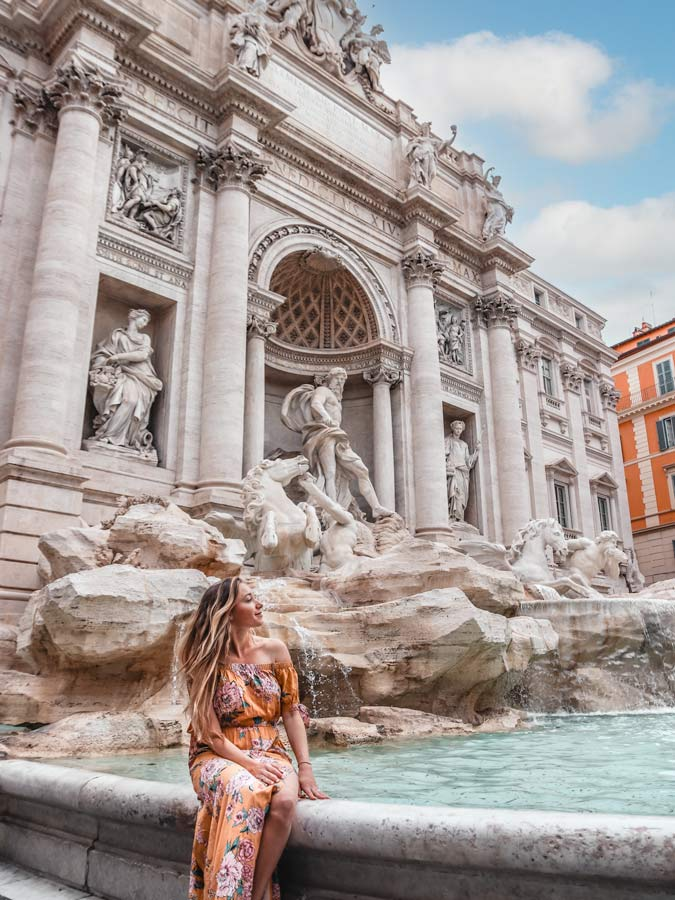 One of the best Photo Spots is Rome's Trevi Fountain. Woman in yellow dress sitting on edge
