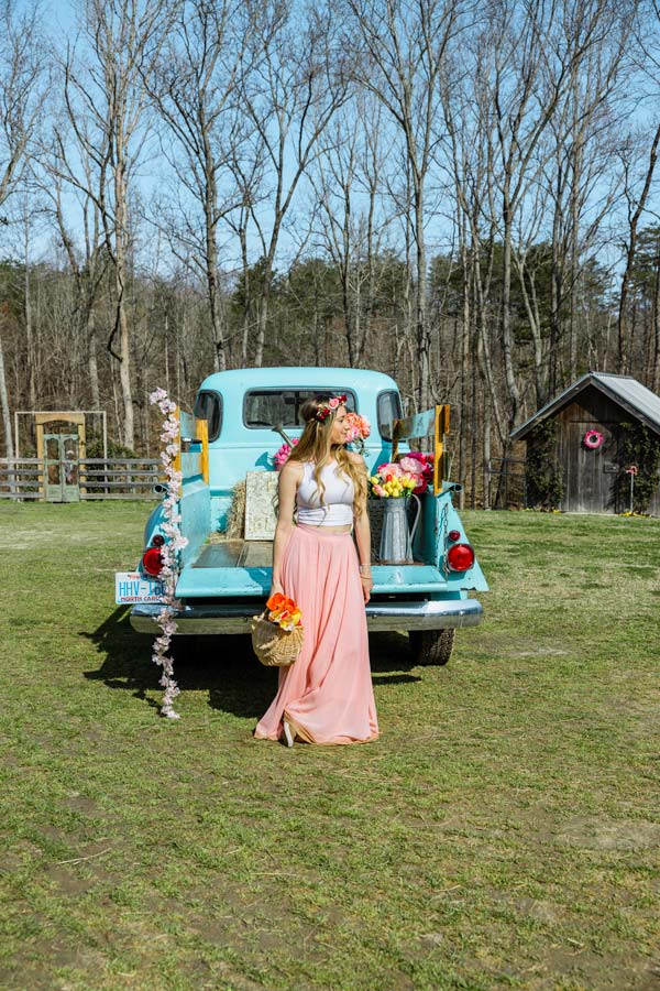 Woman in a pink flowy skirt standing in front of an old fashion powder blue truck with flowers on it.