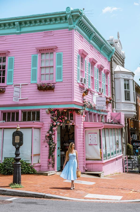 Georgetown in Washington DC is perfect for a weekend trip. Hot pink building with turquoise roof. Woman in blue dress.
