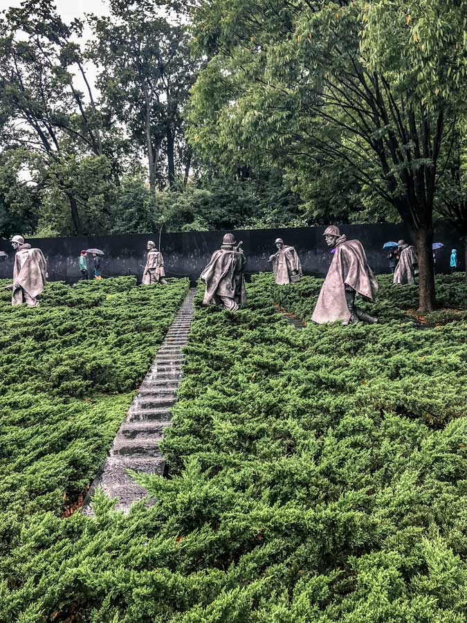 Korean War Memorial on a rainy day. 6 statues of soldiers in view.