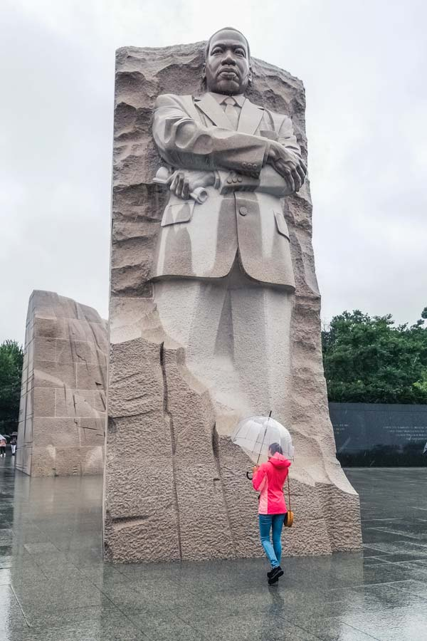 Martin Luther King Jr. Memorial on a rainy day. Woman in pink raincoat and clear unbrella.
