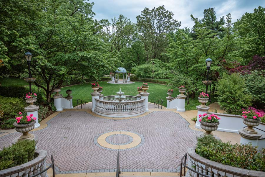 Omni Shoreham Hotel Gardens. Pink flowers, a fountain in the center and lots of greenery.