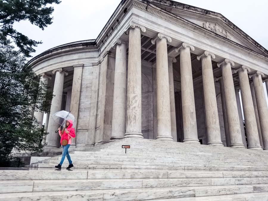 The Thomas Jefferson Memorial on a rainy day. Woman with a hot pink raincoat and umbrella.