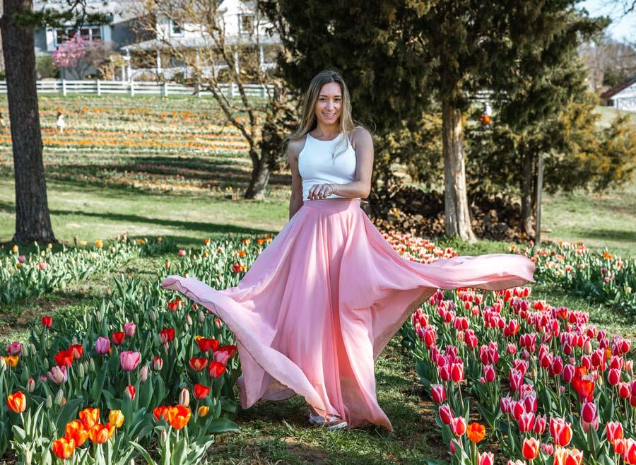 Sam Opp - NC tulip fields wearing pink skirt and white top.