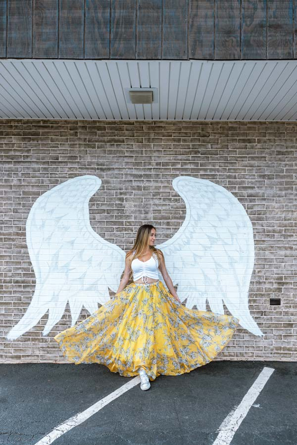 Posing in front of the Winged Mooresville Mural is one of the best things to do in Mooresville, NC