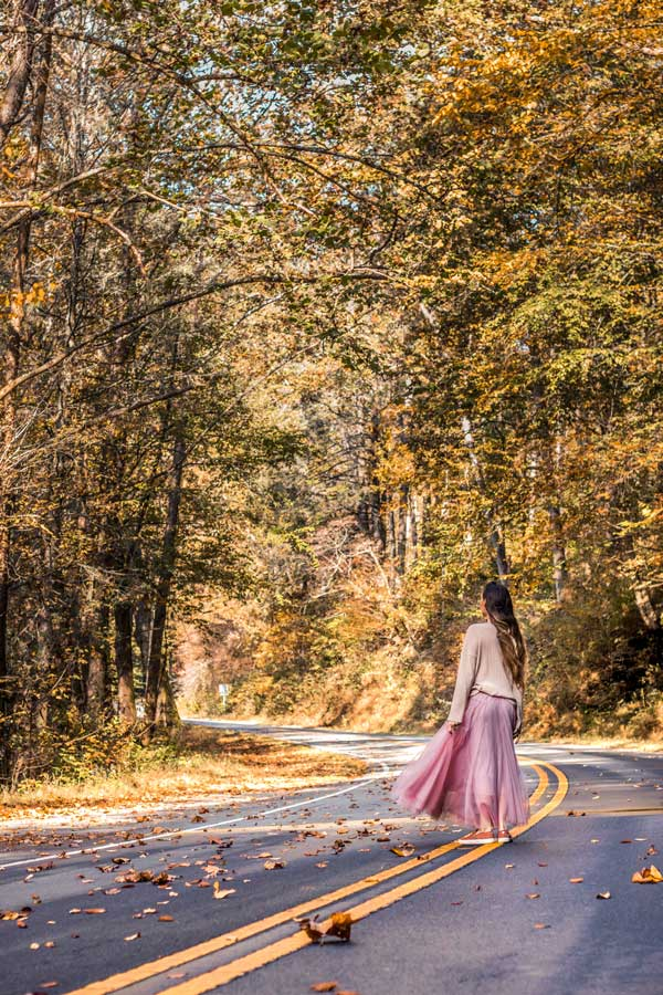 Fall in the Blue Ridge Parkway. Women wearing pink skirt in the middle of the road