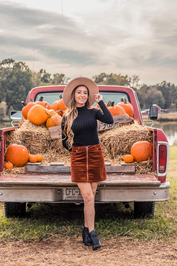 Pumpkin display in the back of a vintage pick up truck at Family Farm Avent Ferry in Holly Springs NC. Woman wearing black long sleeve shirt and corduroy brown skirt.